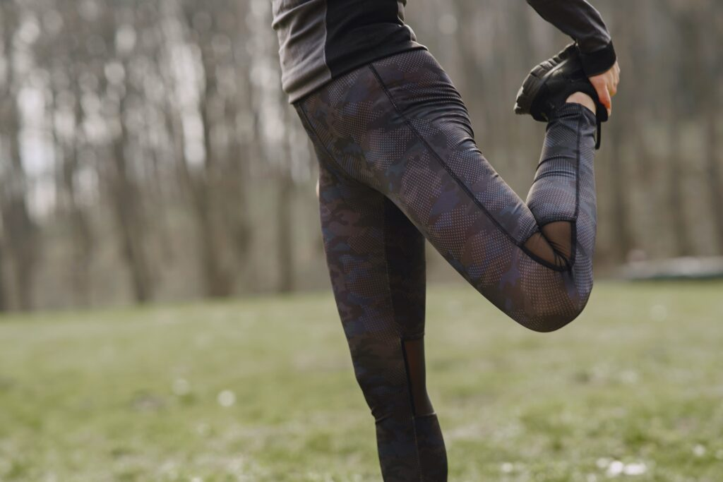 Close up of a woman stretching her quad. Trail running helps make a runner more resilient and injury-resistant.