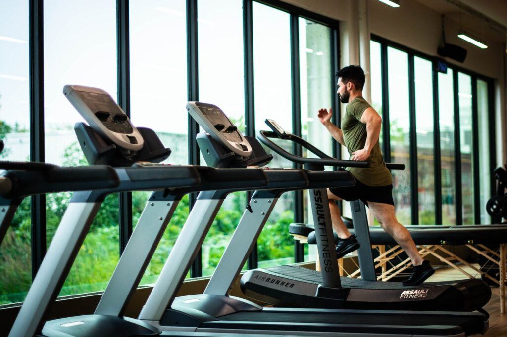 A man running on a treadmill, with several other treadmills in view. While you can go to a gym to run, you definitely don't have to.