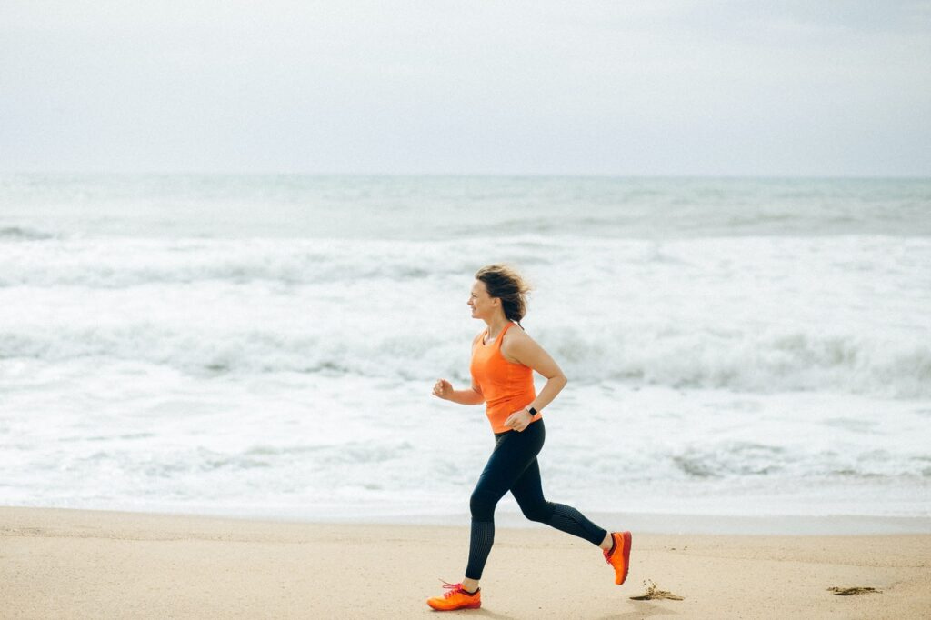 A woman running outside at the beach for her mental health.