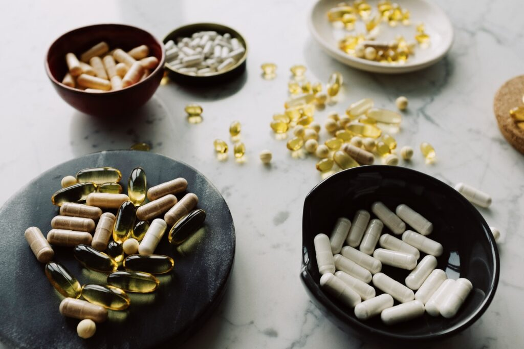 A variety of pills on a table. Supplements are a common tool used for recovery, and there is little evidence they work.